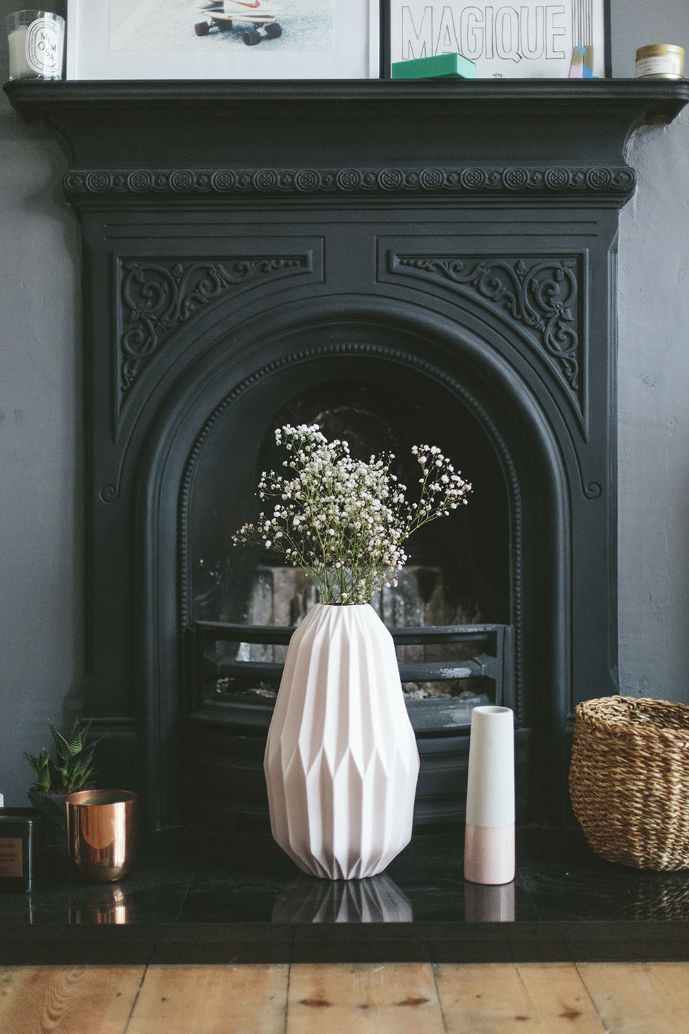 Light pink vase with flowers in front of a dark fireplace