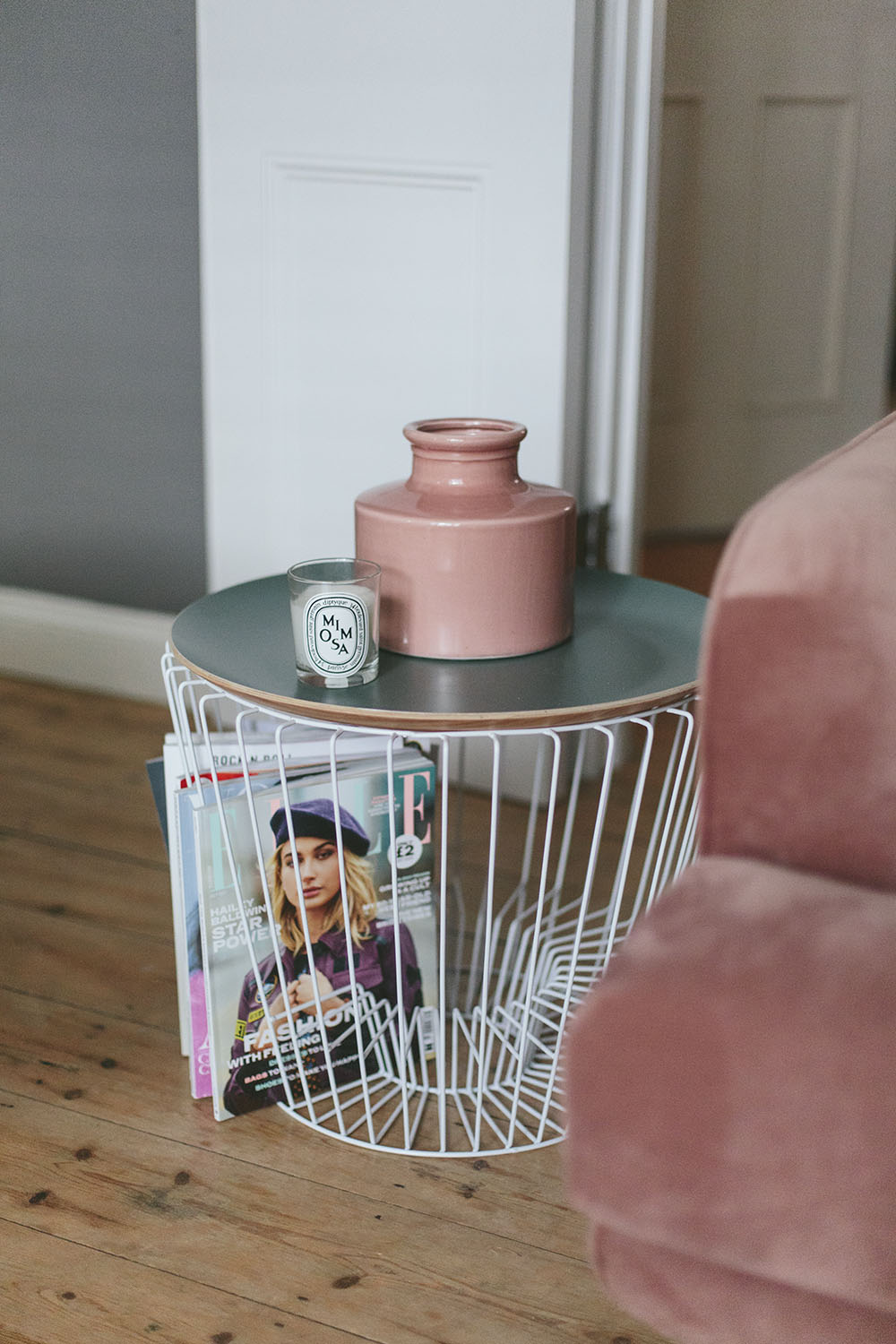 A pink velvet sofa next to a side table and magazine rack with a pink vase on top of it