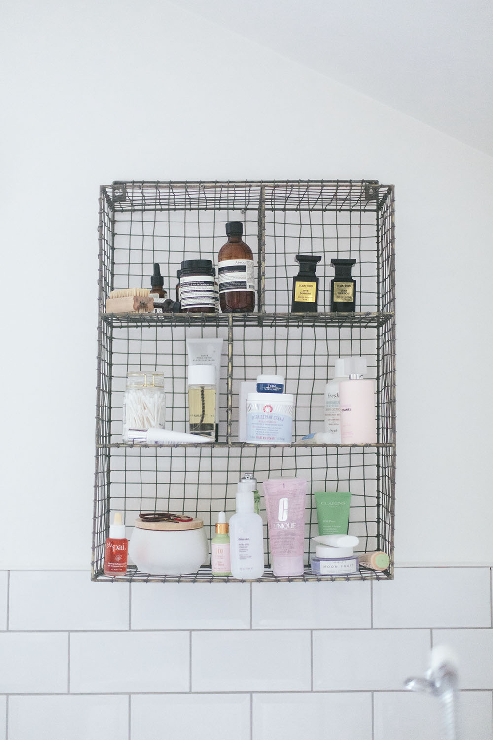 A wire shelf in a bathroom on a white tiled wall