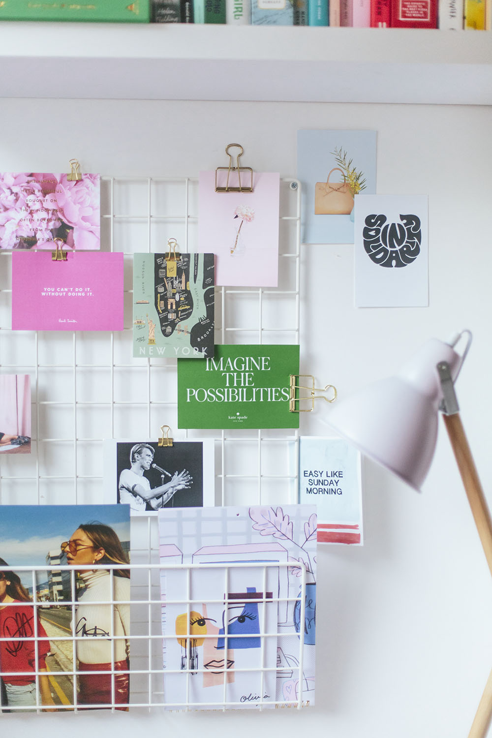 A wire noticeboard with colourful postcards in an office