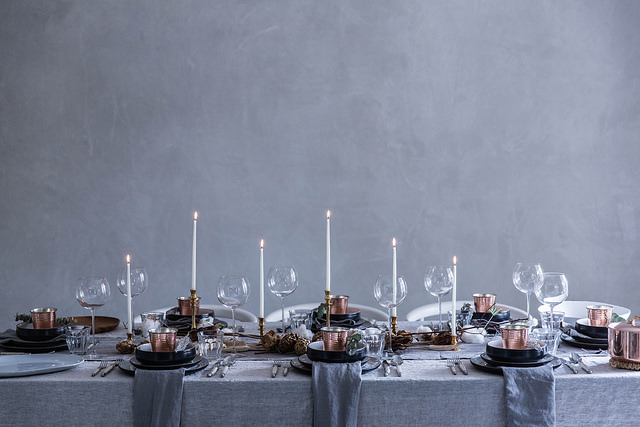 A festive table in shades of grey and cream against a grey backdrop