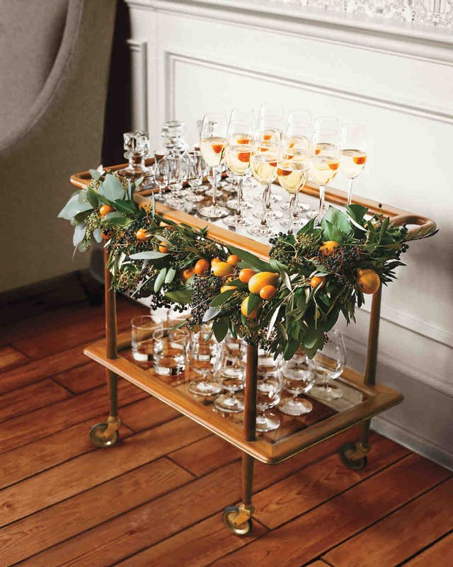 A bar cart carrying glasses and decorated with festive foliage