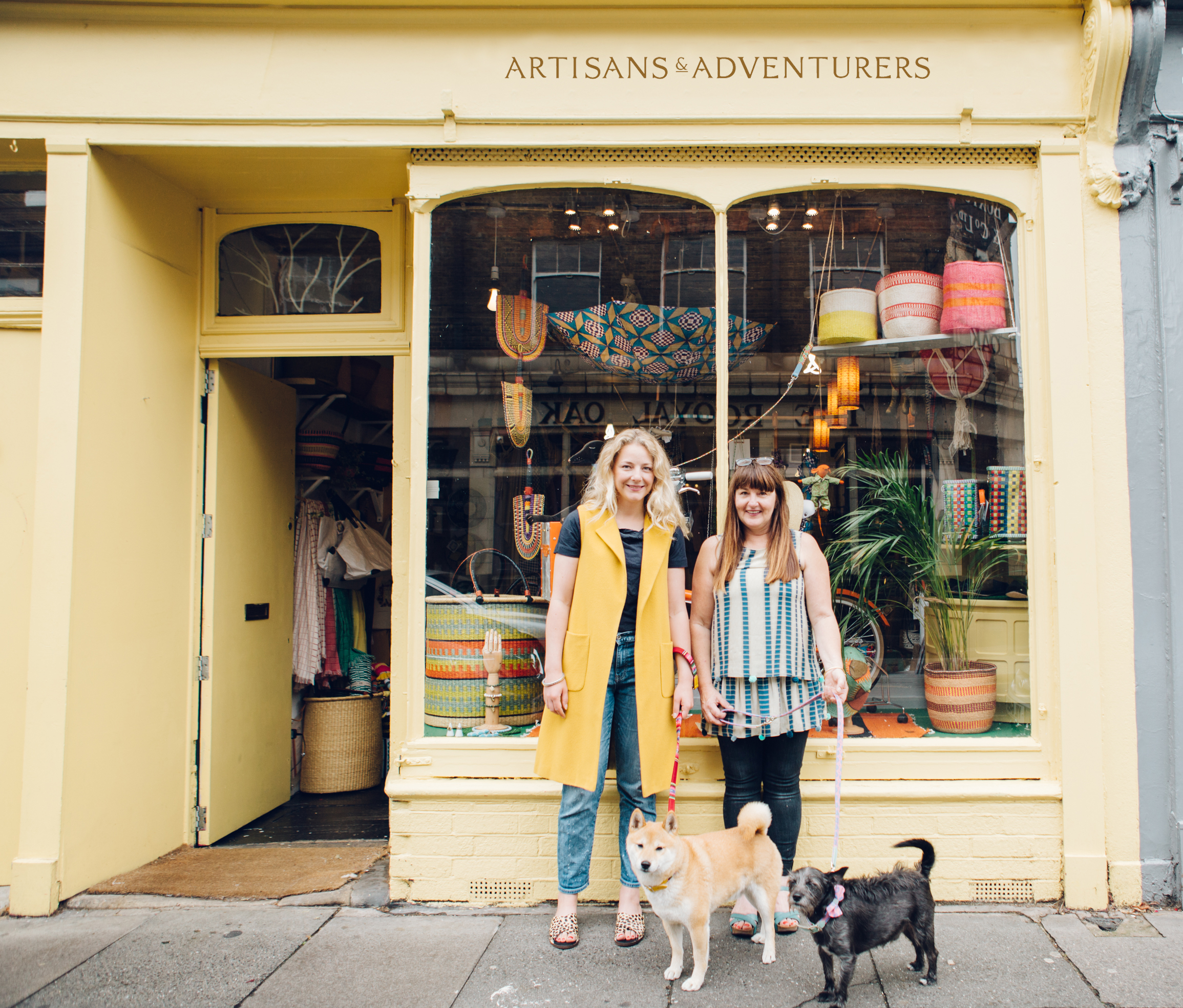 Two dogs and two women outside a lemon yellow shop in Columbia Road