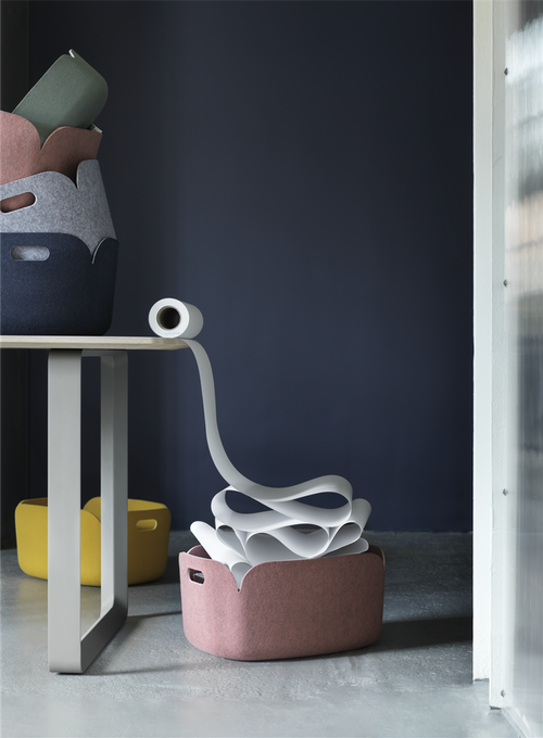 A roll of kitchen paper unrolling off a table into a pink Muuto Restore felt basket.