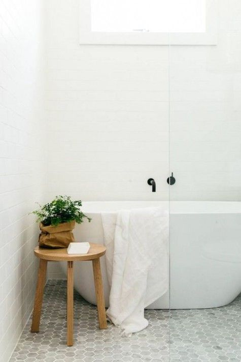 White bathtub with a glass shower screen next to a small stool and potted plant