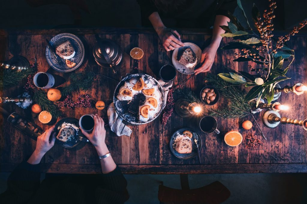 An overhead image of people dining at a festive dinner table