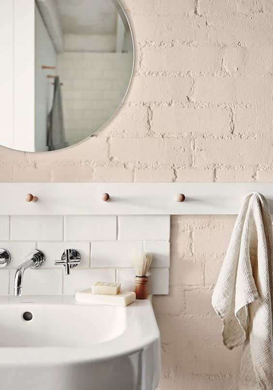 A pink wall with four wooden bathroom hooks, one holding a hand towel.
