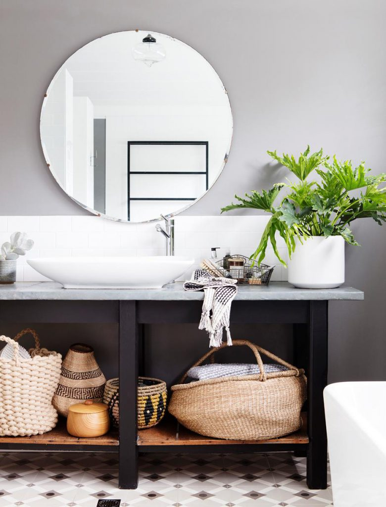 A large circular mirror hangs above a bathroom unit, with a sink, decorative plants, and baskets.
