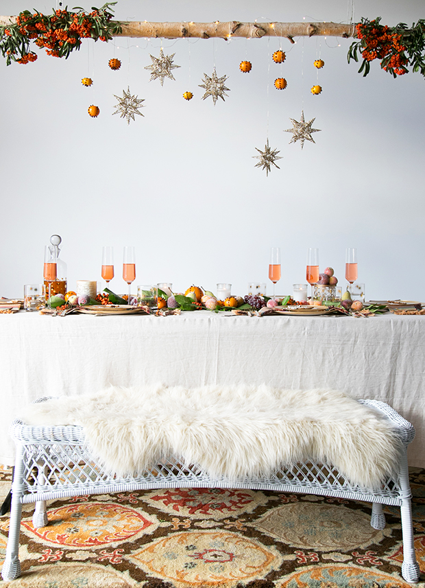 An elevated centrepiece of stars and clementines hangs from a wooden beam over a festively decorated dinner table