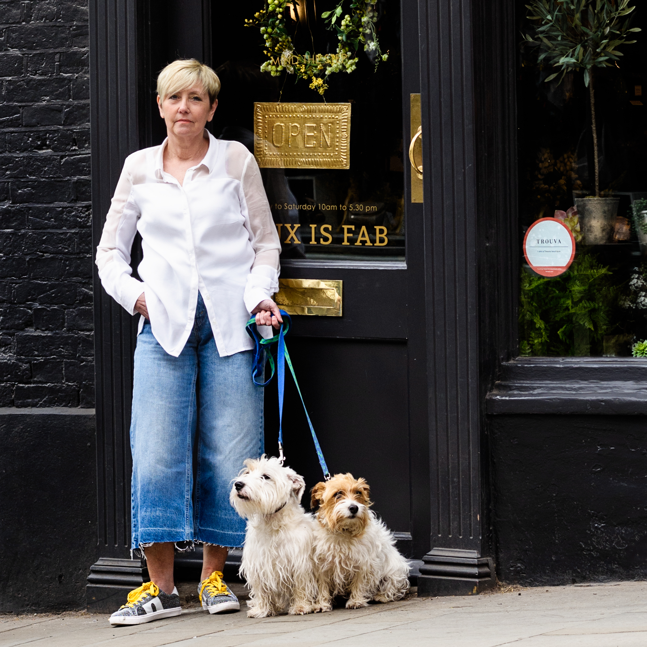 A woman and her two dogs outside her independent shop