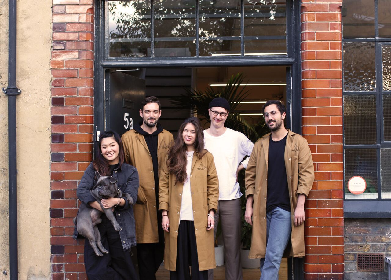 Three men, two women and a grey dog standing in the doorway of an independent shop