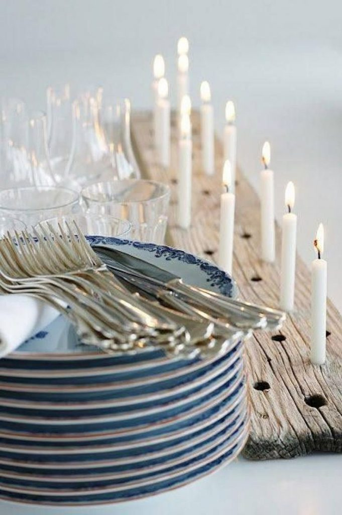 A stack of pale blue plates and gold forks sit beside an arrangement of white candles