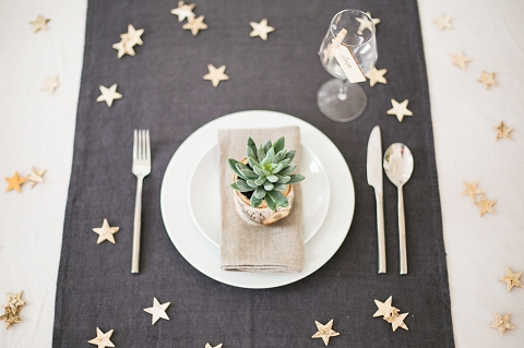 A black table cloth set with white crockery and scattered with gold star-shaped confetti