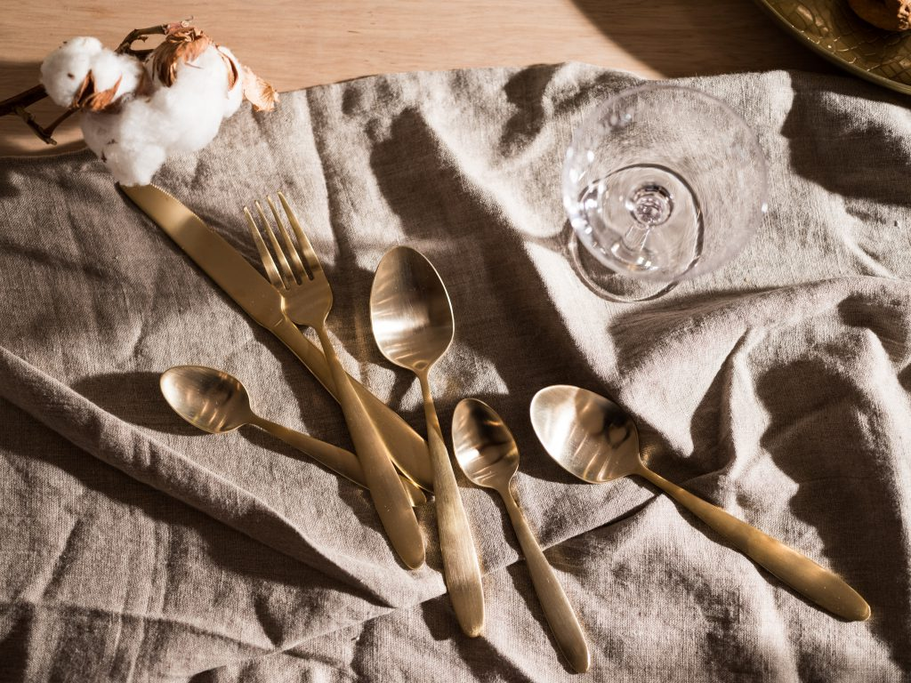 Aerial shot of linen table cloth, gold cutlery, and champagne saucer