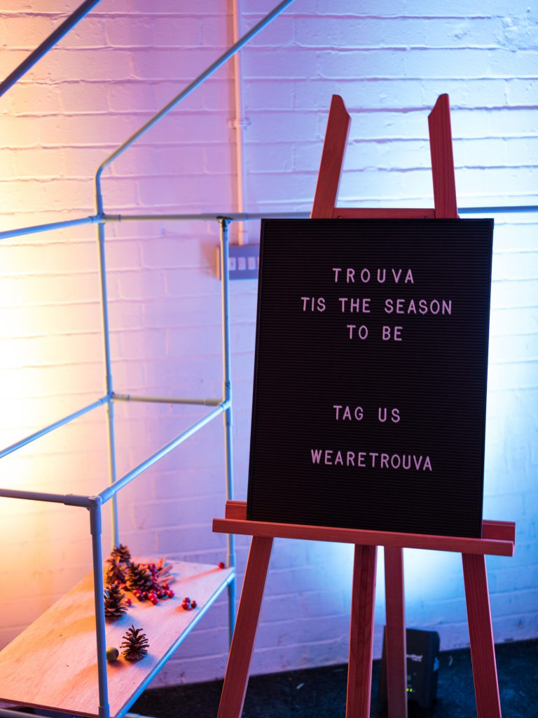 """Message board with the words """"Trouva, Tis the Season to Be, Tag Us WeAreTrouva"""""""