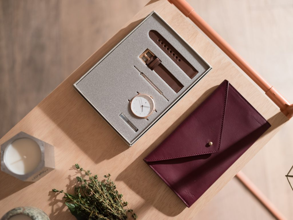 Aerial shot of a watch kit, and a burgundy leather clutch
